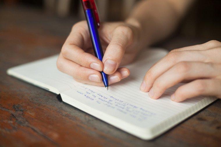 un baiat care scrie intr-un jurnal pe o masa de lemn